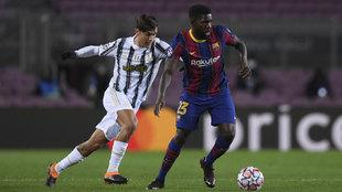 Umtiti, del Barcelona, protege el balón en un duelo con Dybala, de la...