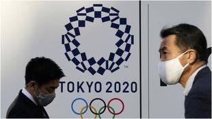 Dos personas con mascarilla delante de un cartel de Tokio 2020.