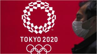 Una persona pasa con mascarilla por delante del logo de Tokio 2020.