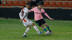 Messi tries to dribble past Mario Fernandez
