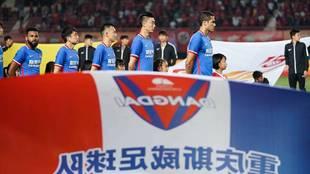 Los futbolistas del Chongqing Dangdai Lifan escuchan el himno antes de...