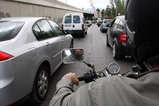 Un motorista avanza entre vehículos en una vía congestionada.