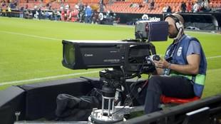 Un cámara de televisión en un partido de fútbol.