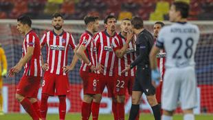 Los jugadores del Atlético protestan al árbitro.