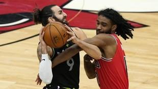 Ricky Rubio trata de proteger el balón de la defensa de Coby White.