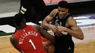 Zion Williamson y Giannis Antetokounmpo luchan por un balón.