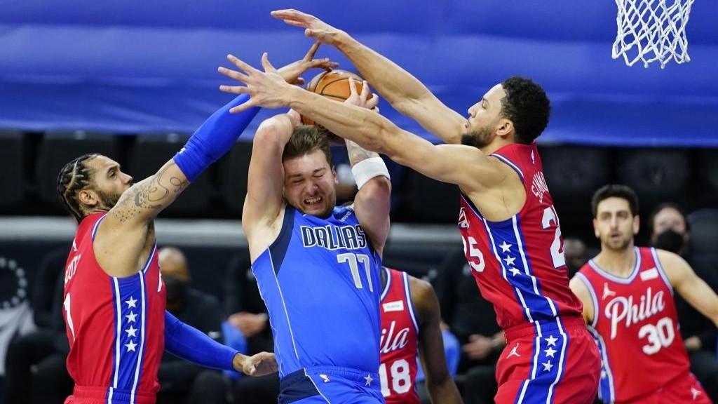 Luka Doncic entra a canasta entre la defensa de Mike Scott y Ben...