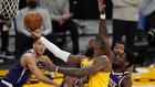 LeBron James de los Lakers intenta anotar una bandeja ante la defensa...