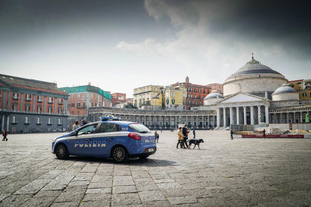 Un coche de policía vigila una plaza semidesierta en Nápoles, de nuevo en zona de riesgo de la pandemia