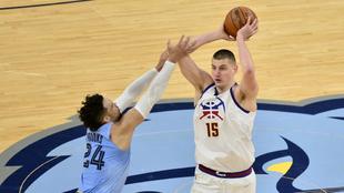 Nikola Jokic, de los Nuggets, intenta pasar el balón ante la...