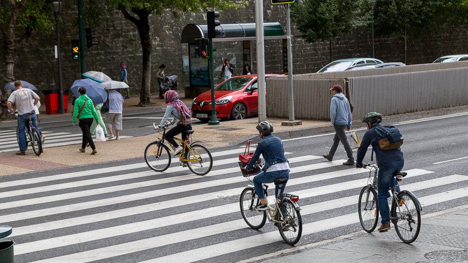 Varios ciclistas cruzan una calle por un paso de cebra sin bajarse de la bici.