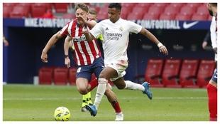 Rodrygo avanza con el balón ante la presencia de Marcos Llorente...