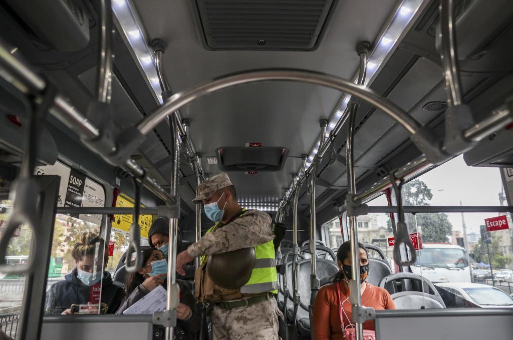 Un soldado controla los permisos de movilidad en un autobúis en Chile