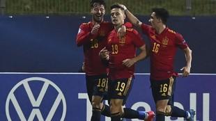 Dani Gómez es felicitado por dos compañeros tras marcar un gol ante...