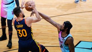 Stephen Curry, de los Warriors, intenta anotar ante la defensa de...