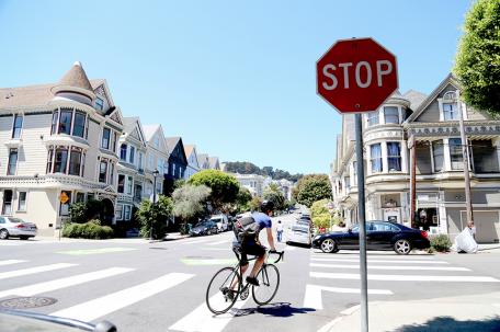 Un ciclista gira a la derecha en un cruce con una señal de Stop.