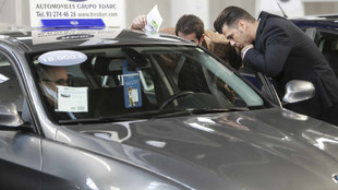 Dos hombres miran un coche de segunda mano en una feria de ocasión.