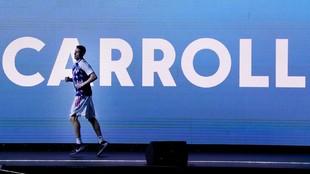 Jaycee Carroll pasa por delante de una gran pantalla con su nombre.