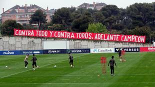 Los jugadores del Atlético entrenando con una pancarta de ánimo al...