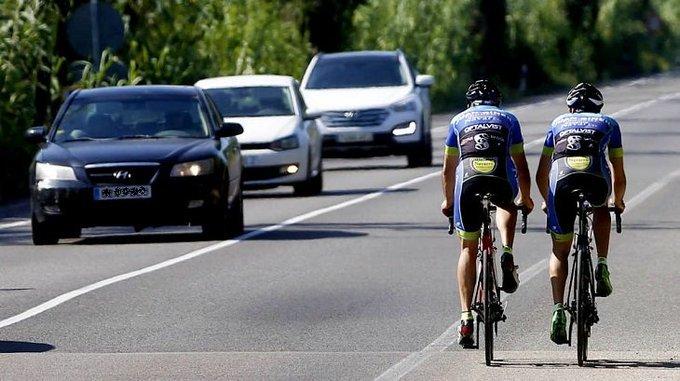 Dos ciclistas circulan por el arcén de una carretera convencional.