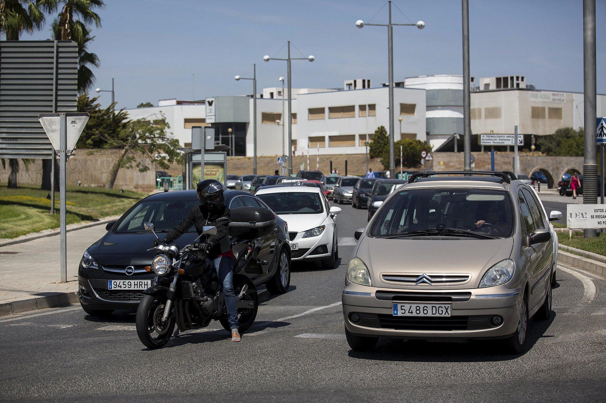 Un motorista se incorpora a una rotonda entre varios turismos.