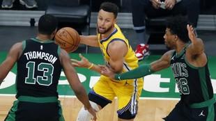 Curry defendido por Thompson y Smart.