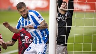 Sipcic intenta dar al balón con la cabeza ante la presencia del meta...