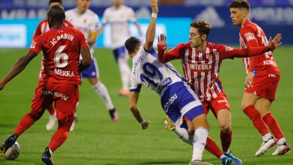 Los defensores sportinguistas rodean al delantero Álex Alegría