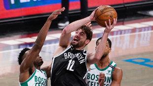 Joe Harris intenta anotar ante la defensa de los Celtics