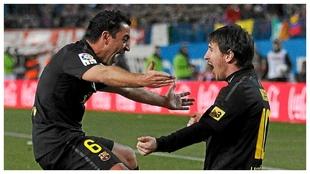 Xavi y Messi se abrazan después de un gol.