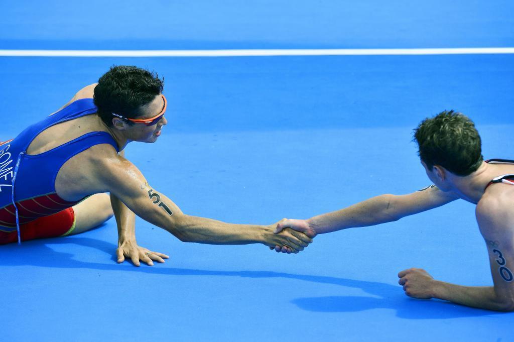 Javier Gómez Noya y Alistair Brownlee, exhaustos, se felicitan tras cruzar la meta