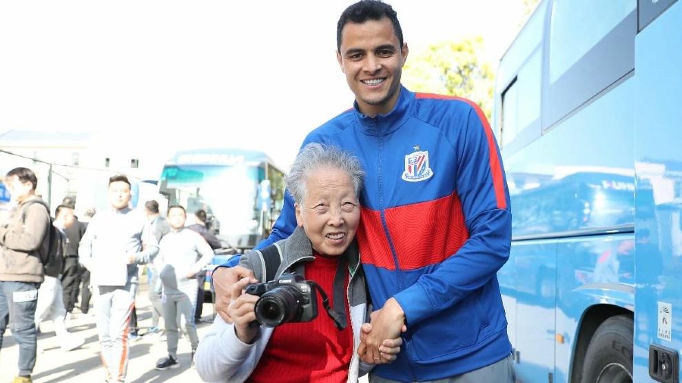 Un sonriente Gio Moreno posa con una veterana aficionada en un evento de puertas abiertas del Shanghai Shenhua