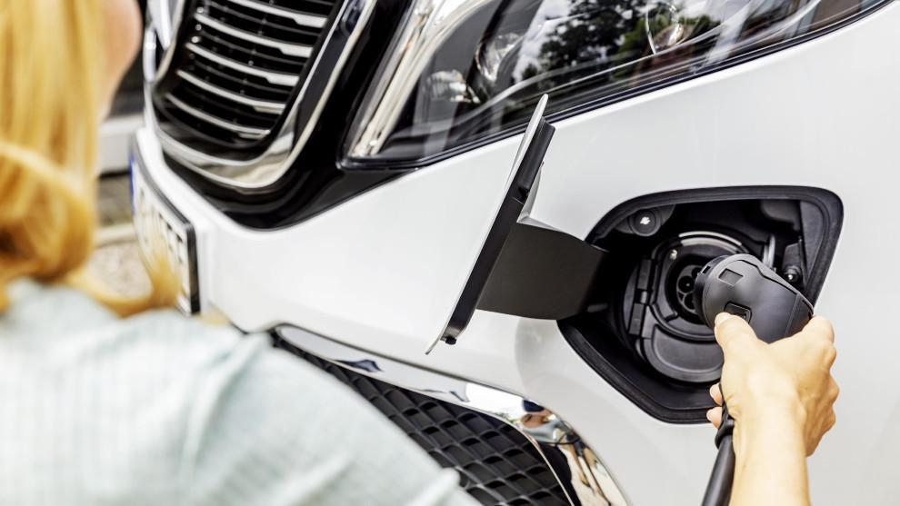 Una mujer conecta su vehículo a un cargador eléctrico.