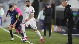 Benzema dirige el balón ante la atenta mirada de Zidane y Jorginho.