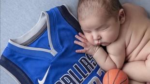 Un recién nacido duerme sobre una camiseta de Doncic.