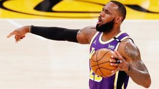 LeBron James marca una jugada a sus compañeros durante un partido de...