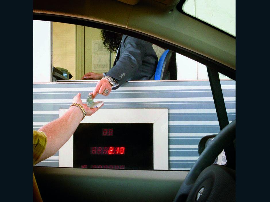 Un conductor paga un peaje en una autopista.