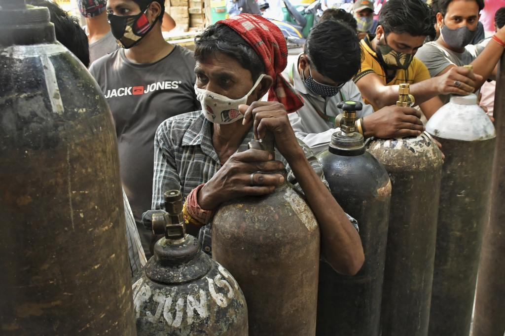 Habitantes de India esperan para rellenar bombonas de oxígeno para respiradores. Hay gran escasez de este materíal médico básico contra el coronavirus en India