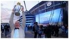 Un fan del Manchester City posa con el trofeo de la Premier a las...