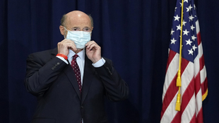 Pennsylvania Gov. Tom Wolf adjusts his face mask.