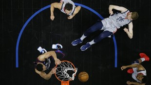 Ben Simmons hace un mate ante la mirada de tres jugadores de los...