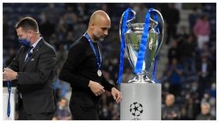 Pep walks past the Champions League trophy.