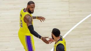 LeBron James y Anthony Davis chocan las manos durante un partido.