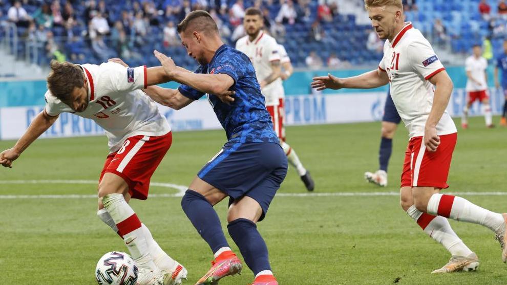 El eslovaco Robert Mak se zafa de dos jugadores polacos, con caño incluido antes de tirar a puerta.