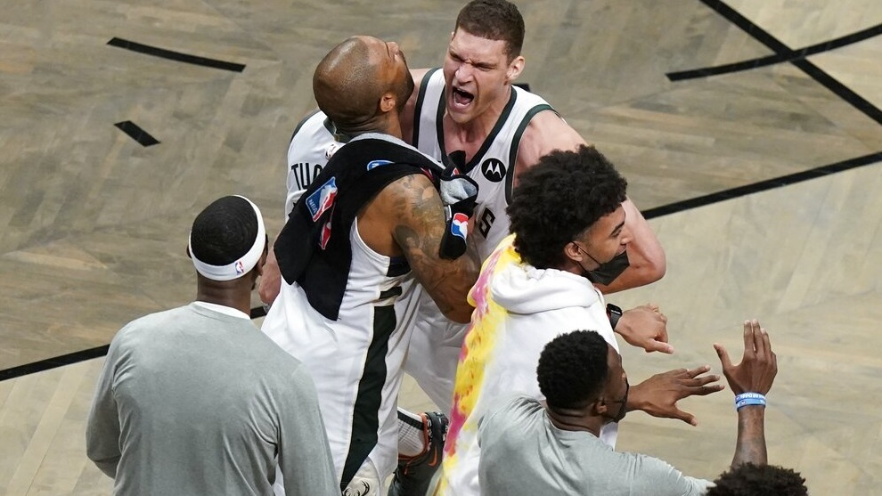 Milwaukee Bucks' Brook Lopez, right, celebrates with P.J. Tucker, left, and other teammates during overtime of Game 7.