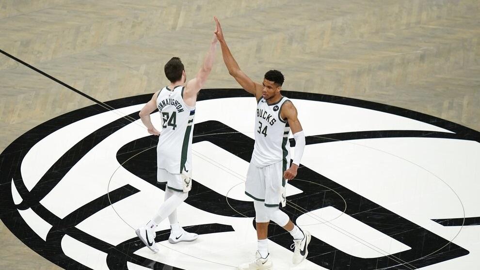 Milwaukee Bucks' Giannis Antetokounmpo (34) celebrates with Pat Connaughton (24).