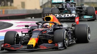 Red Bull driver Max Verstappen, left, leads next to Mercedes driver...