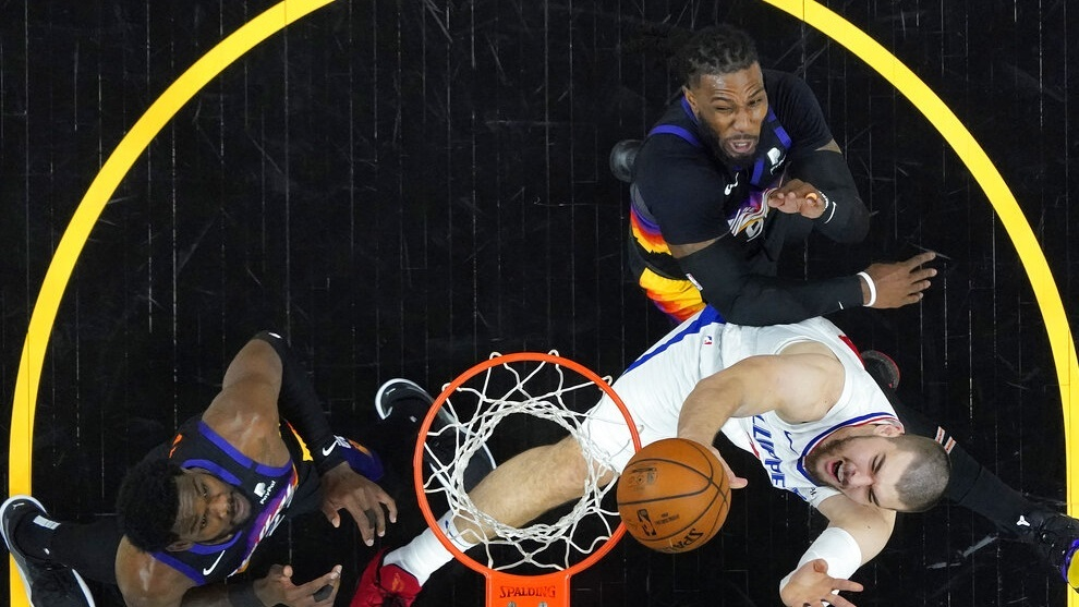 Los Angeles Clippers center Ivica Zubac, right, shoots as Phoenix Suns forward Jae Crowder and center Deandre Ayton, left.