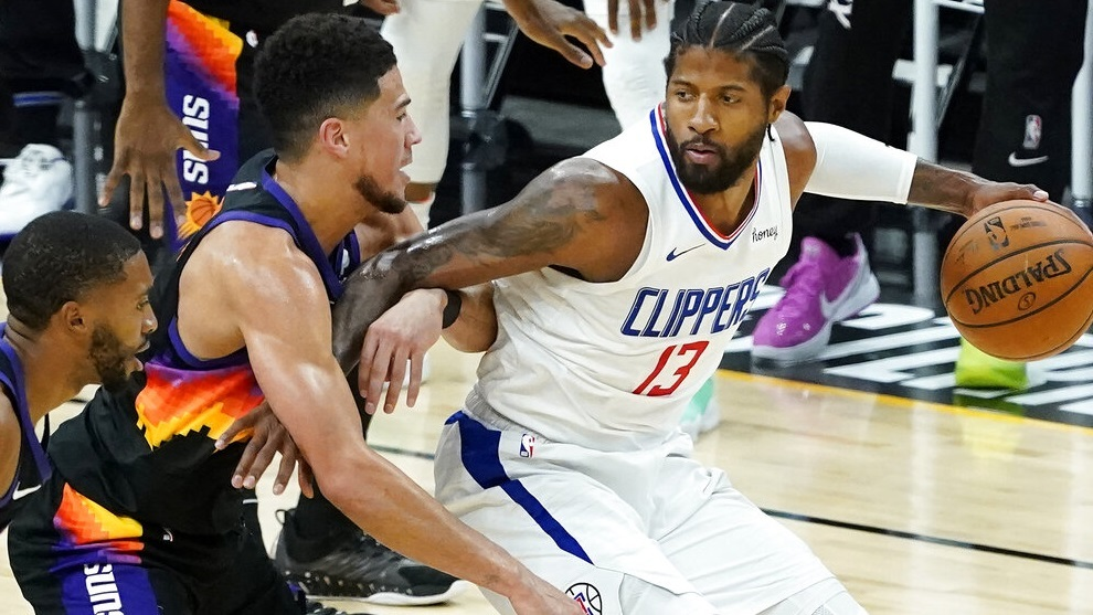 Los Angeles Clippers guard Paul George, right, is defended by Phoenix Suns guard Devin Booker.