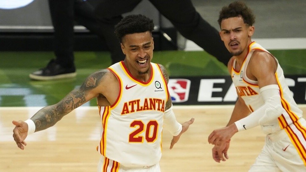 Atlanta Hawks' John Collins reacts after a dunk assisted by Trae Young.